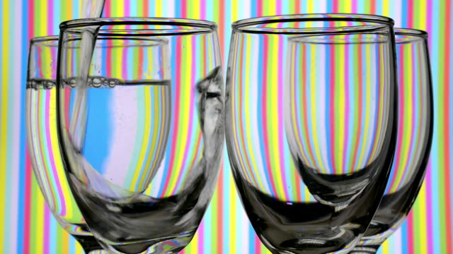light refraction pattern changes when filling drinking glasses with water. - lichtbrechung stock-videos und b-roll-filmmaterial