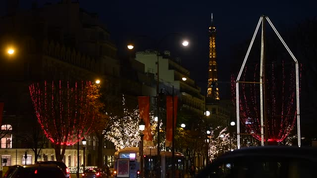light shines from the eiffel tower in the distance as red lights decorate the trees to illuminate the champs-elysees avenue for christmas and new... - avenue stock videos & royalty-free footage