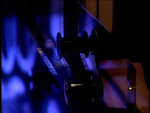 vidéos et rushes de a light shines on film going through a projector. - équipement de projection