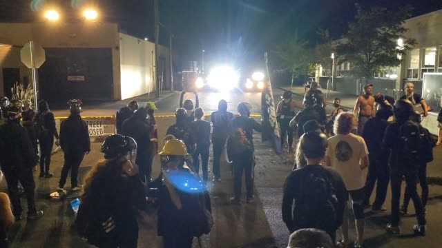 """light shines on protesters behind a closed street as people chant """"quite your job"""" near the north police precinct during a demonstration against... - protestor stock videos & royalty-free footage"""