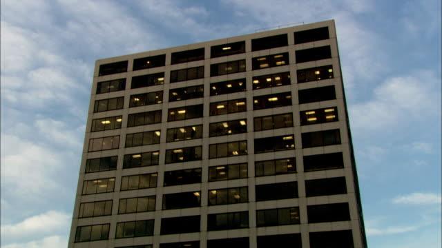 Light shines through dark windows on a high rise in Chicago, Illinois.