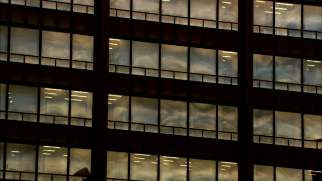 light shines through high rise office building windows in chicago, illinois. - fensterfront stock-videos und b-roll-filmmaterial