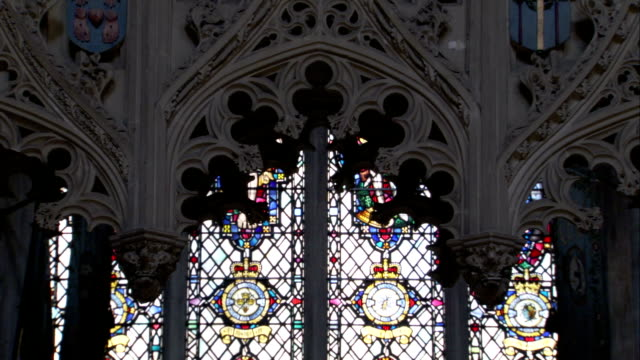 vídeos de stock e filmes b-roll de light shines through stained glass windows in the ely cathedral. available in hd. - idade media