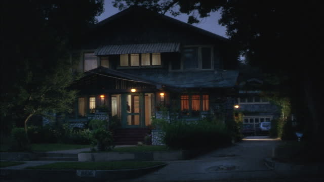 light shines through the windows of a home at night. - front stoop stock videos and b-roll footage
