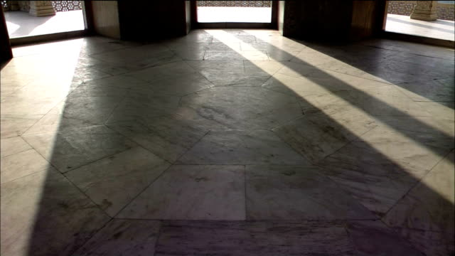 Light shines through windows, casting shadows on the paved floor of Agra Fort in India.