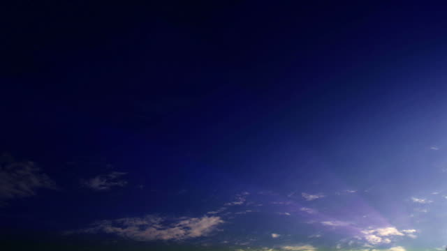 light shoots out from wispy clouds floating across a blue sky. - digital enhancement stock videos & royalty-free footage
