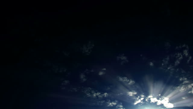 light shoots out from wispy clouds floating across a dark blue sky. - digital enhancement stock videos & royalty-free footage