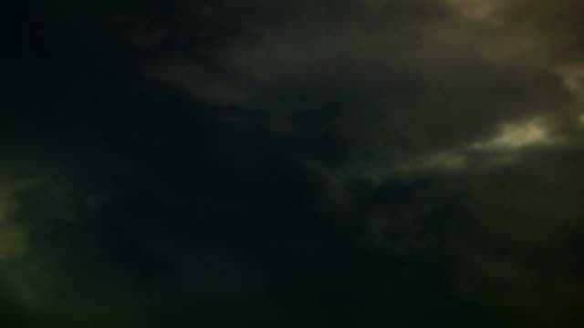 light shoots through storm clouds flying across a moody sky. - digital enhancement stock videos & royalty-free footage