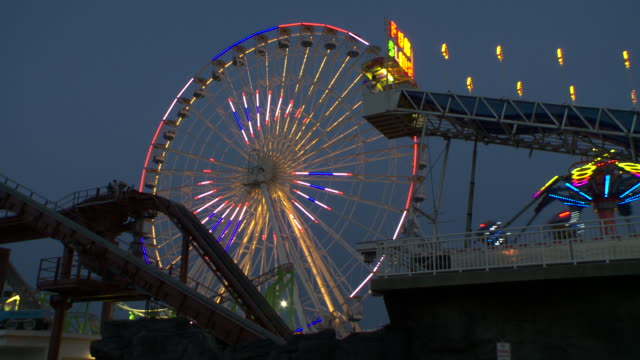 a light show on a ferris wheel at an amusement park on the jersey shore.  other rides are going while  the ferris wheel spins - ferris wheel stock videos & royalty-free footage