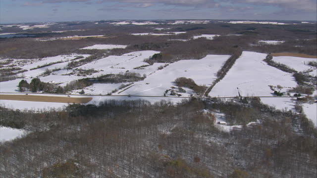 vídeos de stock e filmes b-roll de aerial a light snow covering farmland and woods / new york, united states - rasto de movimento