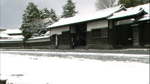 light snow falls as traffic passes the traditional gate in matsue constructed during the edo period in japan. - shimane prefecture stock videos & royalty-free footage