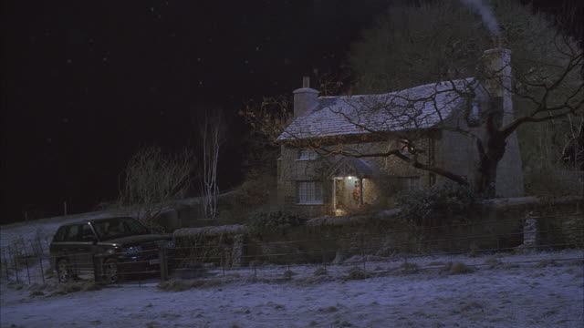 Light snow falls on a country cottage.