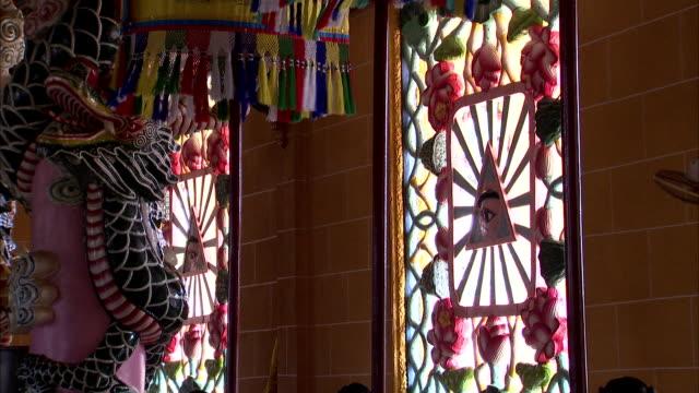 vídeos y material grabado en eventos de stock de light streams through stained glass windows in cao dai temple. - vidriera de colores