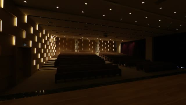 Light switched on/off, in empty conference hall with rows of seats for spectators and audience.