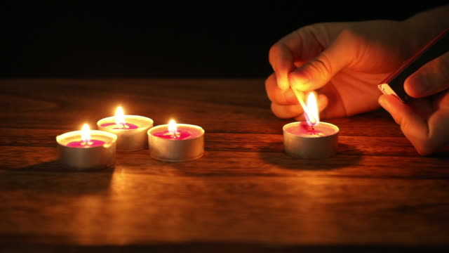 light the scented candle with a match - streichholz stock-videos und b-roll-filmmaterial