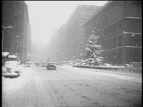 stockvideo's en b-roll-footage met b/w 1948 light traffic on park avenue in snowstorm / nyc / newsreel - 1948