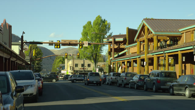 light traffic passes storefronts and parked cars in downtown jackson hole, wyoming. - wyoming stock-videos und b-roll-filmmaterial
