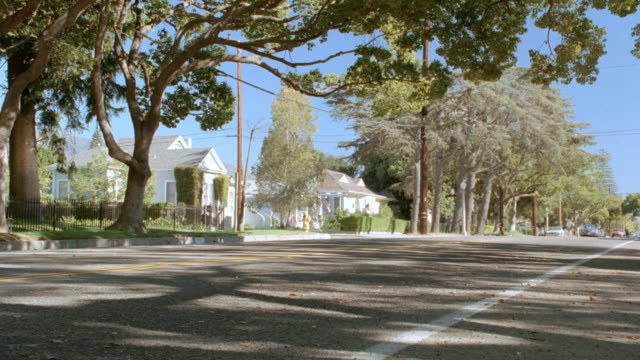 light traffic rolls down a tree-lined street in a small southern town. - traffic点の映像素材/bロール