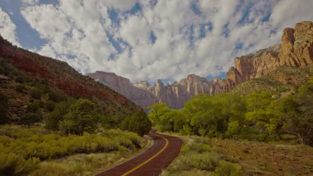 light traffic zooms through majestic zion national park as clouds race over the mountains. - zion national park stock videos & royalty-free footage