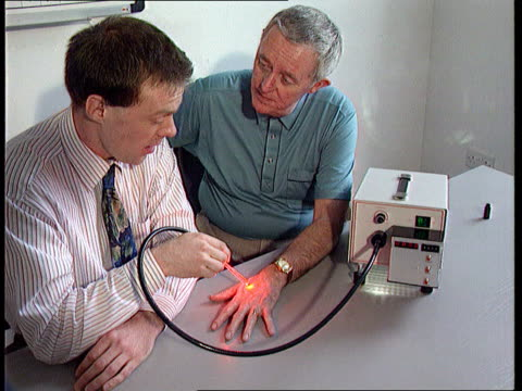 light treatment england cms dr colin whitehurst using new type of lamp to shine light on to male patient's hand cs light on back of hand cms doctor... - tea light stock videos and b-roll footage