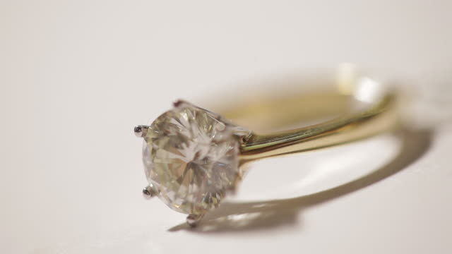 Light twinkles in a diamond set into a gold ring.