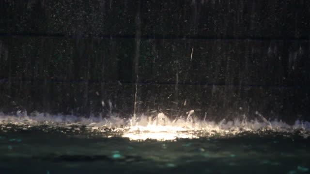 Light under the artificial waterfall