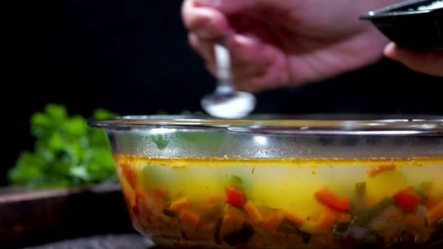 light vegetable soup with fish stock - adding salt stock videos and b-roll footage