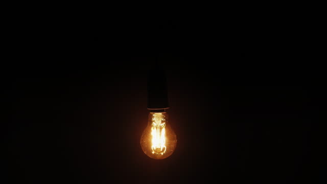 lightbulb. black background. - energy efficient stock videos & royalty-free footage