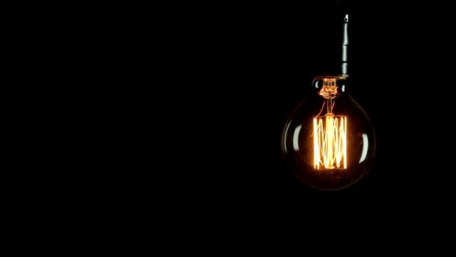 vídeos y material grabado en eventos de stock de bombilla sobre fondo negro-idea concepto - bombilla