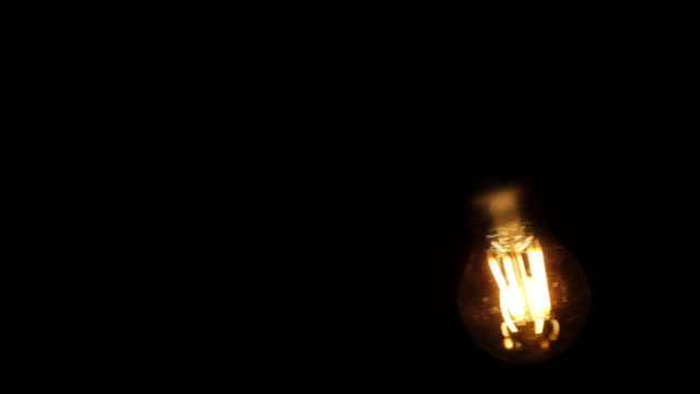 lightbulb swinging. black background. - hanging stock videos & royalty-free footage