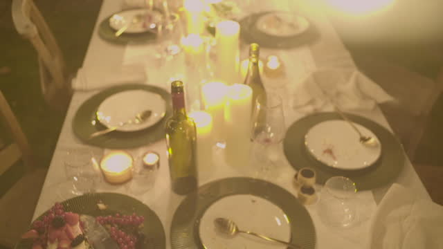lightbulbs hang above an outdoor dinner table - overexposed stock videos & royalty-free footage