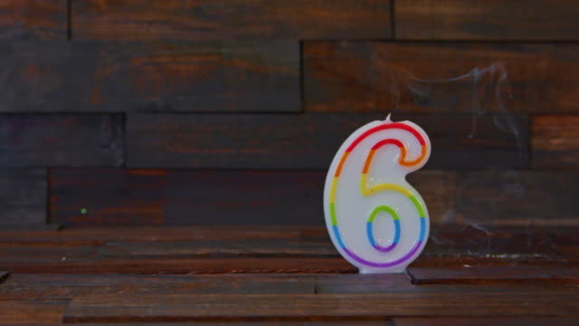 lighted birthday candle number 6 on a rustic wood background. - number 6 stock videos & royalty-free footage