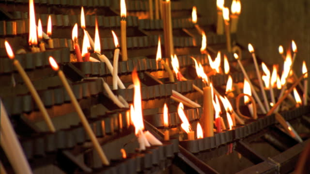 lighted prayer candles vigil lights burning in graduated rows of votive candle holders many long taper candles leaning prayers tradition religion... - votive candle stock videos and b-roll footage