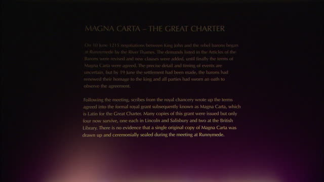 vídeos de stock e filmes b-roll de a lighted sign titled, magna carta-the great charter hangs above an old document. - magna carta documento histórico