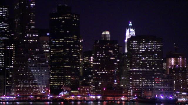 lighted skyscrapers illuminate the skyline of manhattan at night. - manhattan video stock e b–roll