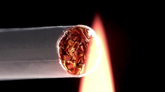 vidéos et rushes de lightert and burning cigarette against black background, real time - cigarette