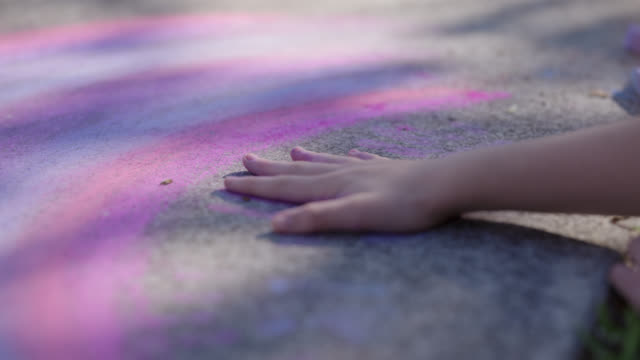 vidéos et rushes de cu lighthearted pre-teen moves their palm across a vibrant chalk rainbow - trottoir