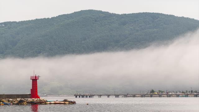 lighthouse and sea fog in jisepohang port area / geoje-si, gyeongsangnam-do, south korea - 水の形態点の映像素材/bロール