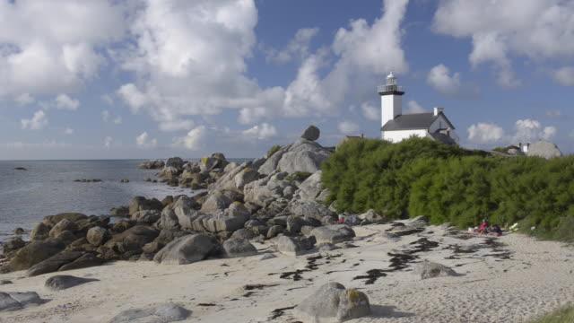 lighthouse at rocky coast - bretagna video stock e b–roll