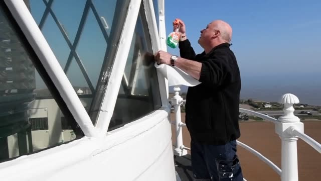 lighthouse attendant chris moore cleans the glass around the lantern room and volunteer stephen burke cleans the 500 watt bulb at happisburgh... - east anglia stock videos & royalty-free footage