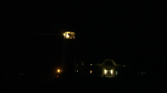 a lighthouse beacon sweeps the night sky. - lighthouse stock videos & royalty-free footage