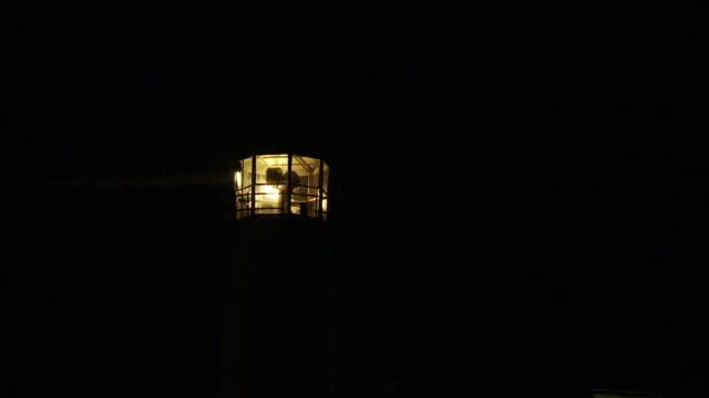 lighthouse beams search a dark sky. - lighthouse stock videos & royalty-free footage