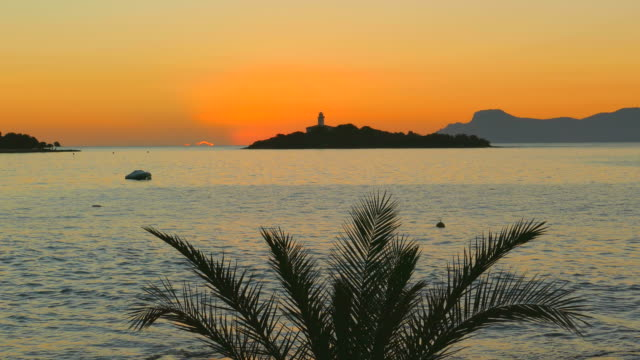 vidéos et rushes de lighthouse in alcanada near port d' alcudia at morning mood, majorca, balearic islands, spain - palmier