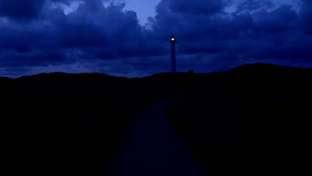 lighthouse in dune landscape with footpath at night, lyngvig fyr, hvide sande, ringkobing fjord, north sea, midtjylland, central jutland, denmark - dusk bildbanksvideor och videomaterial från bakom kulisserna