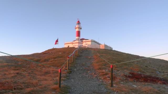 vídeos de stock, filmes e b-roll de lighthouse in magdalena island with chilean flag during sunrise - passear sem destino
