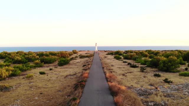 lighthouse in the mediterranean sea at the end of straight road and horizon. faro de formentera con paisaje y carretera durante la puesta de sol. - punto di fuga video stock e b–roll