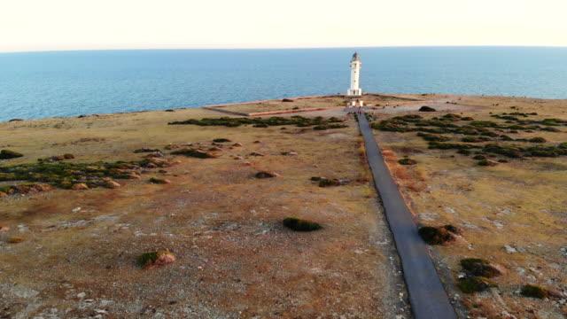 vídeos de stock e filmes b-roll de lighthouse in the mediterranean sea at the end of straight road and horizon. faro de formentera con paisaje y carretera durante la puesta de sol. - beco