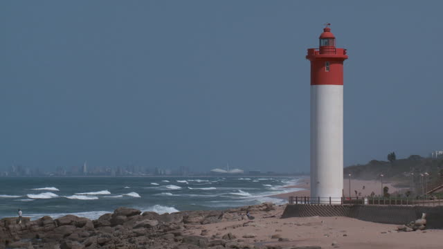 ES Lighthouse next to the shore with the Durban skyline in the distance / Durban, South Africa