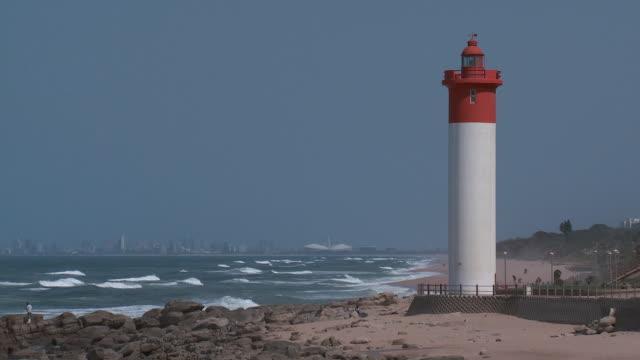 vídeos y material grabado en eventos de stock de es lighthouse next to the shore with the durban skyline in the distance / durban, south africa - kwazulu natal
