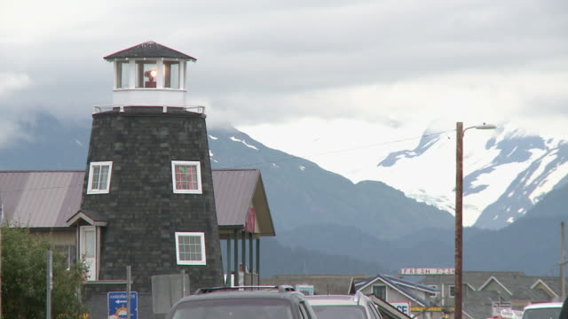 """lighthouse of the salty dawg saloon with light active, cars passing both directions, homer spit, homer, kenai peninsula, alaska, snow capped mountains of kachemak bay state park and wilderness park visible."" - homer alaska stock videos & royalty-free footage"